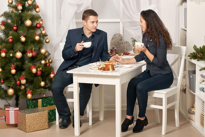 Romantic couple drinking tea with cookies and talking, christmas tree with holiday decoration, new year theme stock image