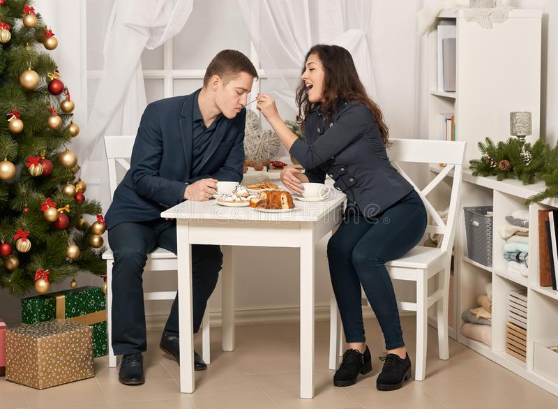 Romantic couple drinking tea with cookies and talking, christmas tree with holiday decoration, new year theme stock images