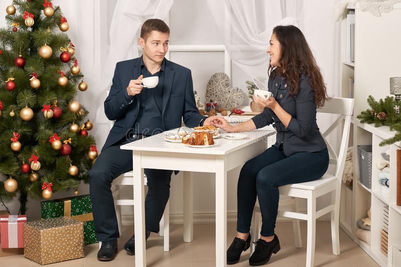 Romantic couple drinking tea with cookies and talking, christmas tree with holiday decoration, new year theme stock photography