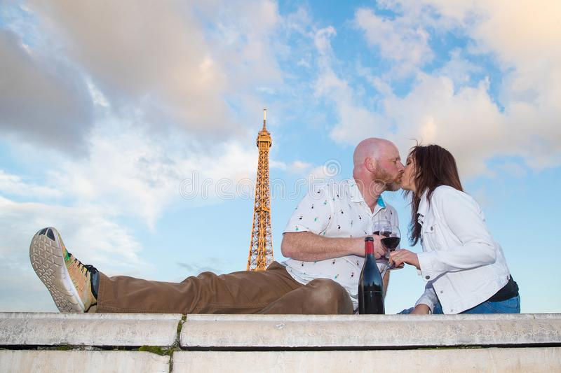 Romantic couple kissing under the Eiffel Tower in Paris, France. Romantic couple drinking wine and kissing near the Eiffel Tower in Paris, France royalty free stock images