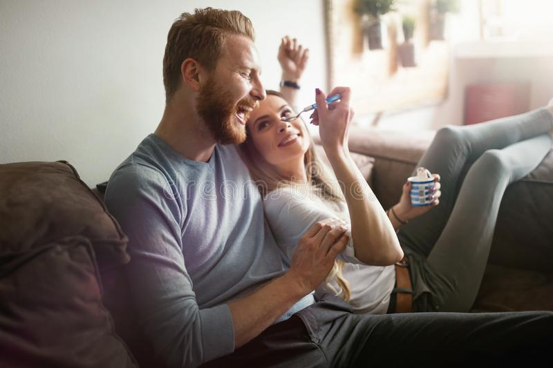 Romantic couple eating ice cream together and watching tv. Romantic couple in love eating ice cream together and watching tv royalty free stock photos