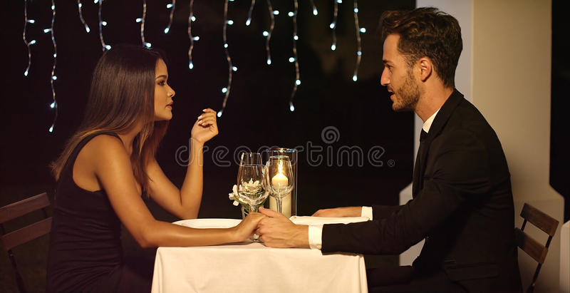 Romantic couple enjoying an evening dinner. At an upmarket restaurant sitting chatting and holding hands side view stock photos
