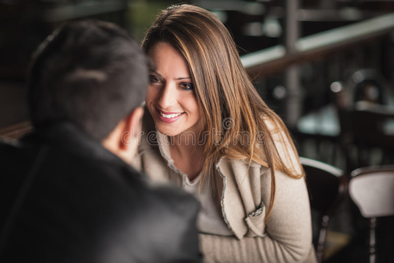Romantic couple flirting at the bar. Romantic young couple dating and flirting at the bar, staring at each other's eyes stock photo
