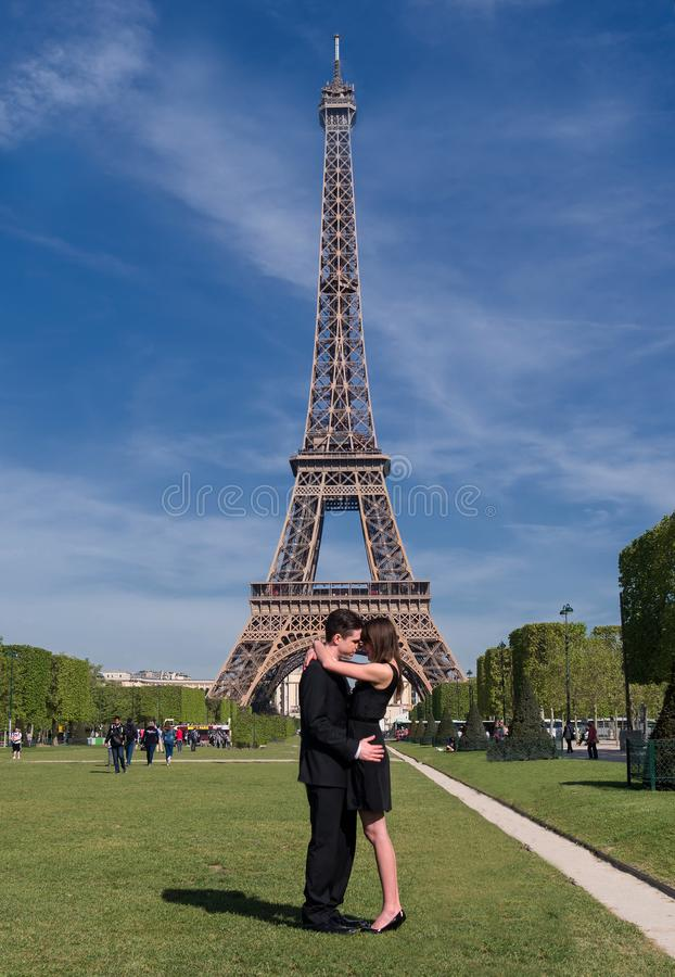 A romantic young couple soulful hug and takes a photo in front of the Eiffel Tower in Paris, France. A romantic sight under the Eiffel Tower, A couple embrace royalty free stock image