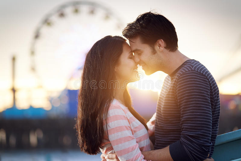 Romantic couple in front of santa monica at sunset royalty free stock image