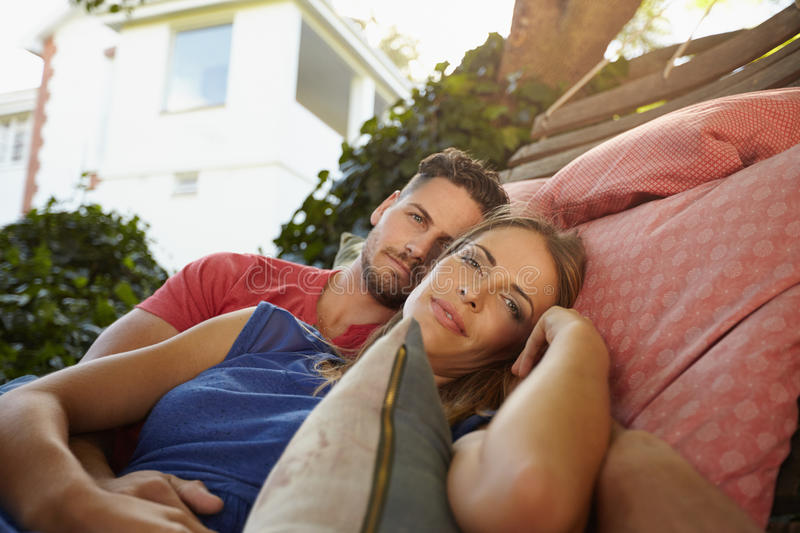 Romantic couple in garden hammock together. Romantic young caucasian couple relaxing on a hammock together and looking at camera. Young men and women on garden stock image