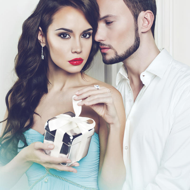 Romantic couple with gift. Fashion photo of beautiful romantic couple with gift royalty free stock image