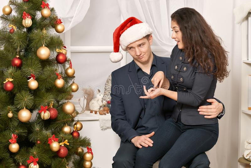 Romantic couple having fun - the girl is sitting on Santa, wants many gifts and makes wishes. Christmas tree with holiday decorati. On, new year theme stock photo