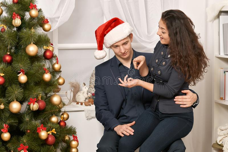 Romantic couple having fun - the girl is sitting on Santa, wants many gifts and makes wishes. Christmas tree with holiday decorati. On, new year theme stock images