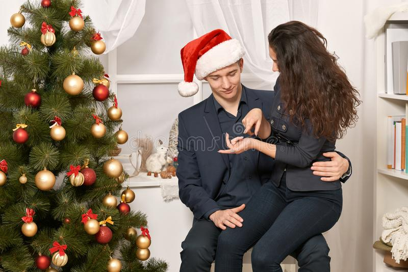 Romantic couple having fun - the girl is sitting on Santa, wants many gifts and makes wishes. Christmas tree with holiday decorati. On, new year theme royalty free stock photo