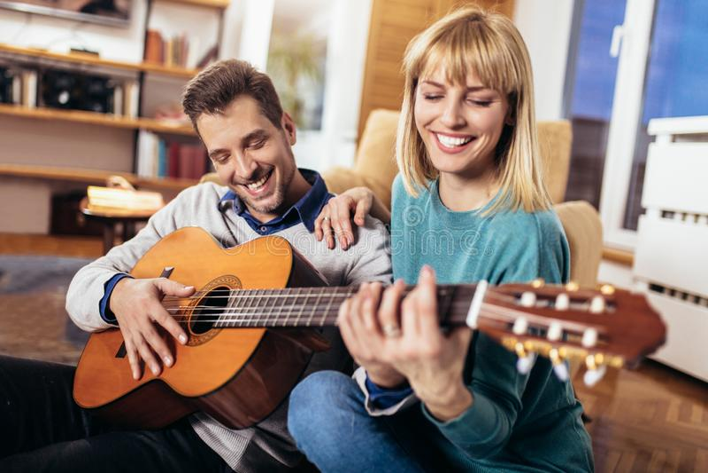 Couple having fun at home, man playing guitar. Romantic couple having fun at home, men playing guitar royalty free stock images