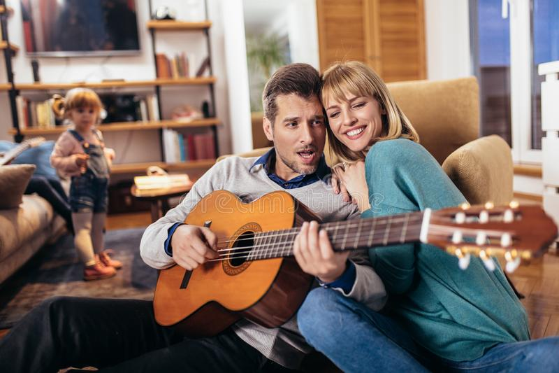 Couple having fun at home, man playing guitar, child in background. Romantic couple having fun at home, men playing guitar, child in background royalty free stock image