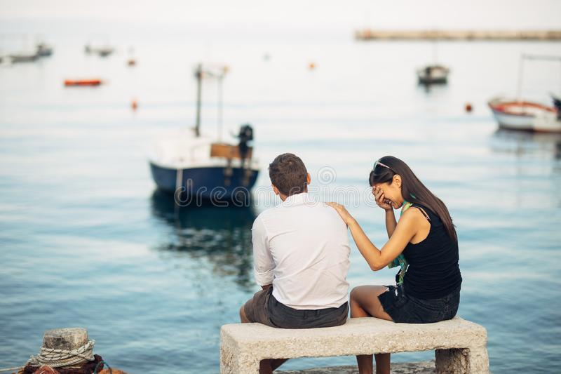 Romantic couple having relationship problems.Woman crying and begging a man.Fisherman life,dangerous occupation.Navy sailors royalty free stock images