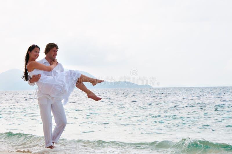 Romantic couple having a walking on the sea shore. Picture of romantic young couple having a walking on the sea shore royalty free stock photography