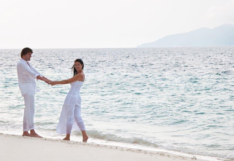 Romantic couple having a walking on the sea shore. Picture of romantic young couple having a walking on the sea shore stock photography