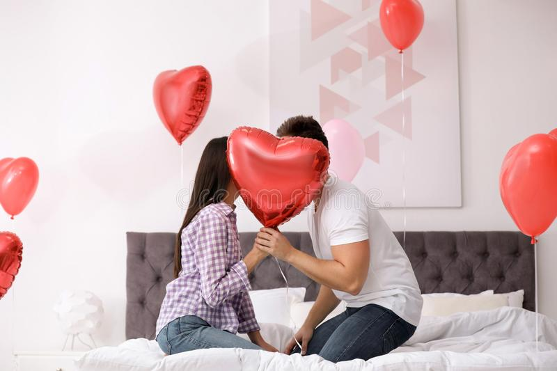 Romantic couple hiding behind heart balloon in bedroom. Valentine`s day celebration. Romantic couple hiding behind heart shaped balloon in bedroom. Valentine`s stock images