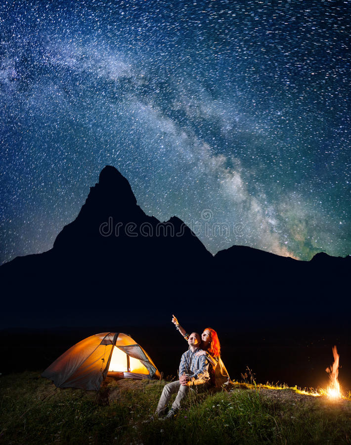 Romantic couple hikers looking at the shines starry sky at night. Happy pair sitting near camp and campfire. Milky way and silhouette of high mountains on the stock images