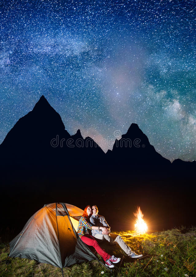 Romantic couple hikers looking to the shines starry sky and Milky way in the camping at night near campfire. On the background silhouette of the high mountains royalty free stock image