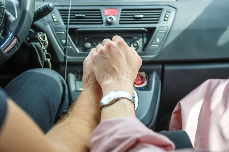 Romantic couple holding hands in car. Lovers or newlywed married young couple in romance. wedding theme.  stock photography