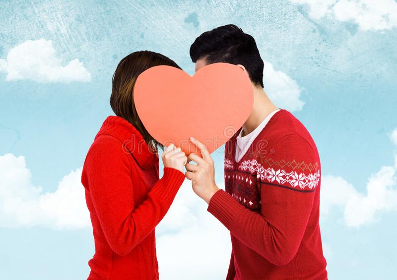 Romantic couple holding heart shape and kissing each other stock photo