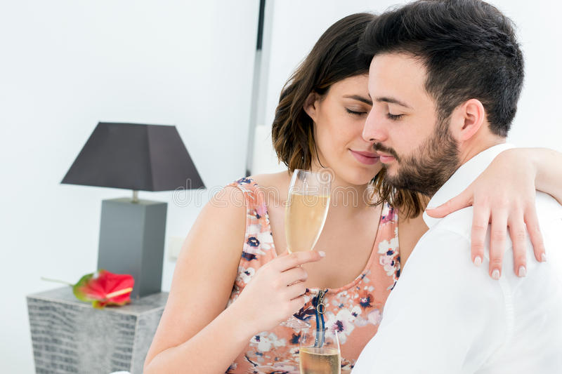 Romantic couple in hotel room with sparkling wine. royalty free stock photos