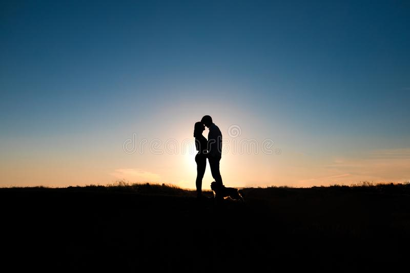 Romantic couple hug at sunset on background. The silhouette of romantic couple hug at warm sunset light on background. Concept of love and life stock image