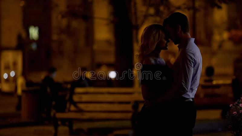 Romantic couple hugging and enjoying city park date in the evening, love. Stock photo royalty free stock photo