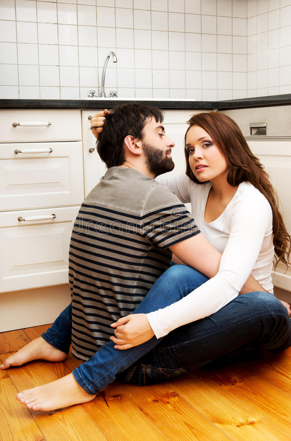 Romantic couple hugging in the kitchen. Young beautiful couple embracing in the kitchen stock photography