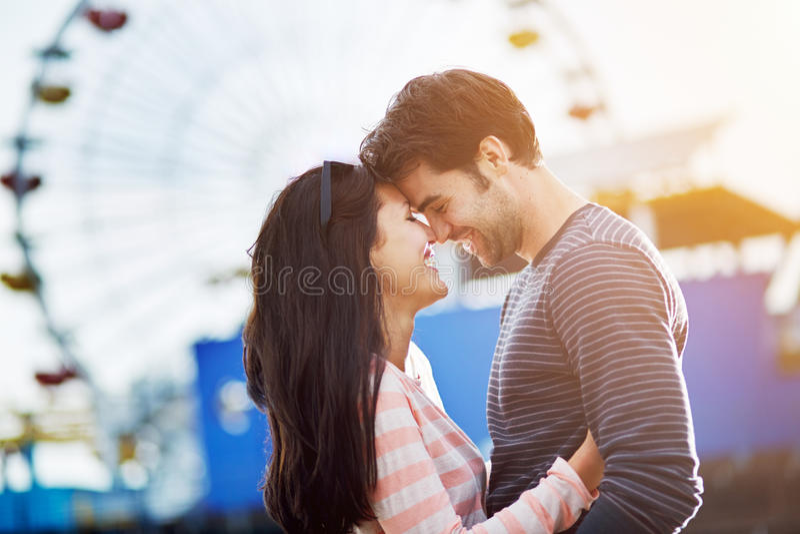 Romantic couple infront of santa monica. Romantic couple embracing with santa monica pier in background stock image