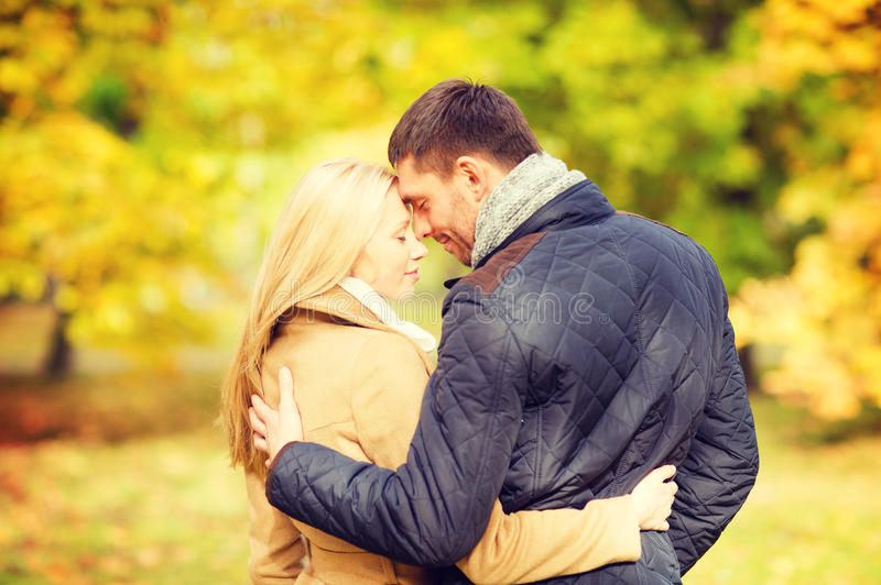 Romantic couple kissing in the autumn park. Holidays, love, travel, relationship and dating concept - romantic couple kissing in the autumn park stock photos