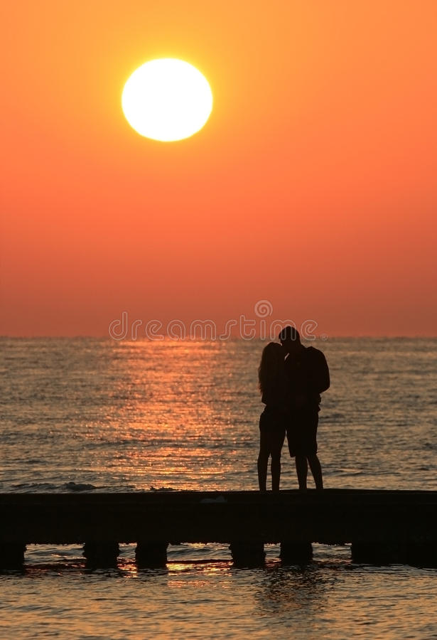 Romantic couple kissing at sunset royalty free stock photos