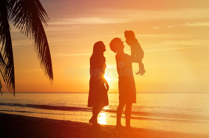 Romantic couple with little child at sunset beach stock photos