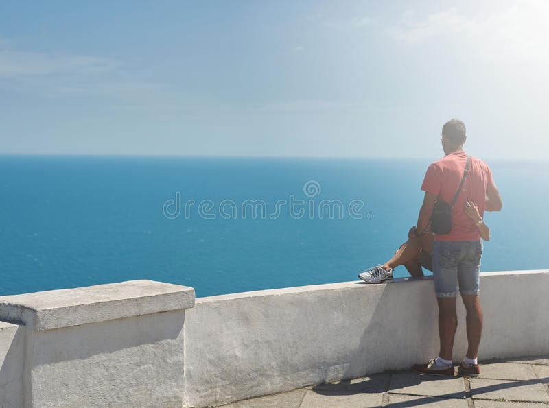 Romantic couple looking at the sea. A loving couple on a viewing platform gently hug and look at the sea stock photo