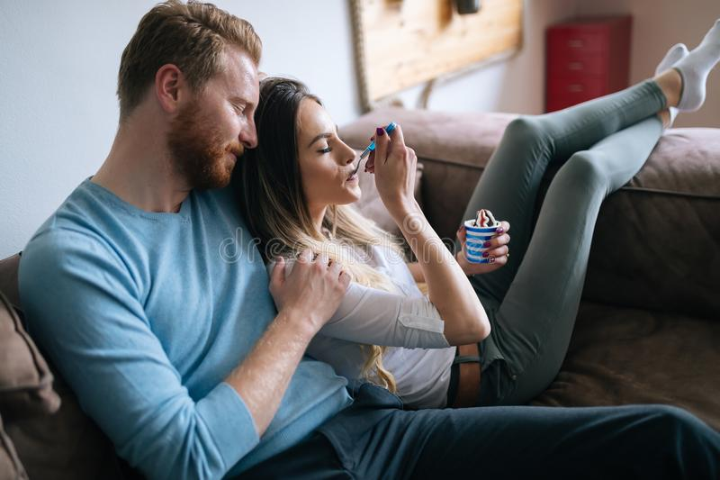 Romantic couple eating ice cream together and watching tv stock image
