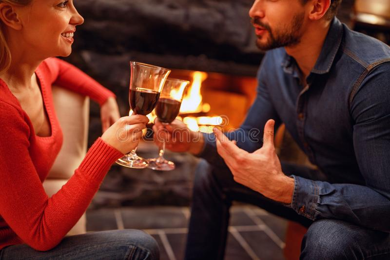 Romantic couple in love enjoying in wine near fireplace royalty free stock image