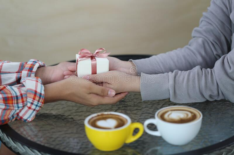 Romantic couple in love hand holding holding gift box and two cups of latte art with pattern the heart on table in coffee shop stock photo