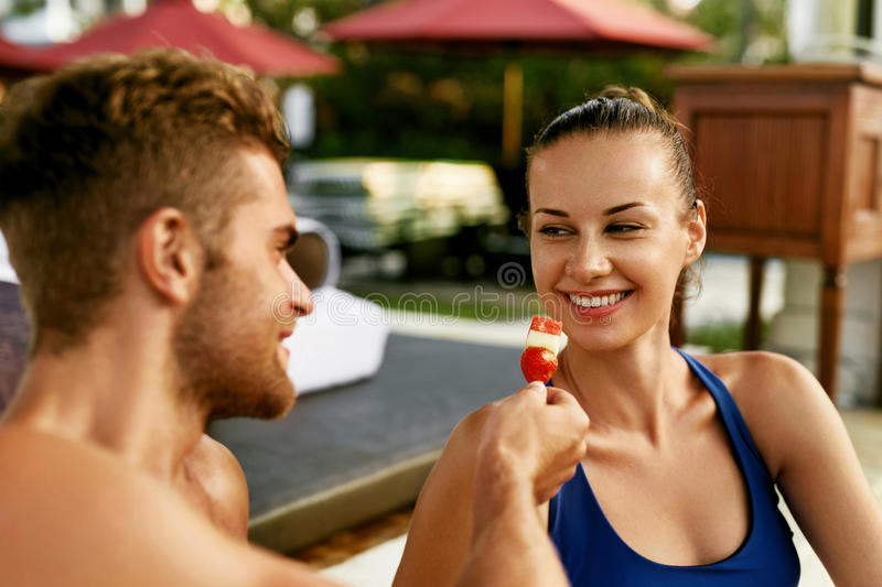 Romantic Couple In Love Having Fun Together Feeding Each Other. Strawberries Outdoors. Handsome Happy Man And Beautiful Smiling Woman On Summer Travel Vacation royalty free stock image
