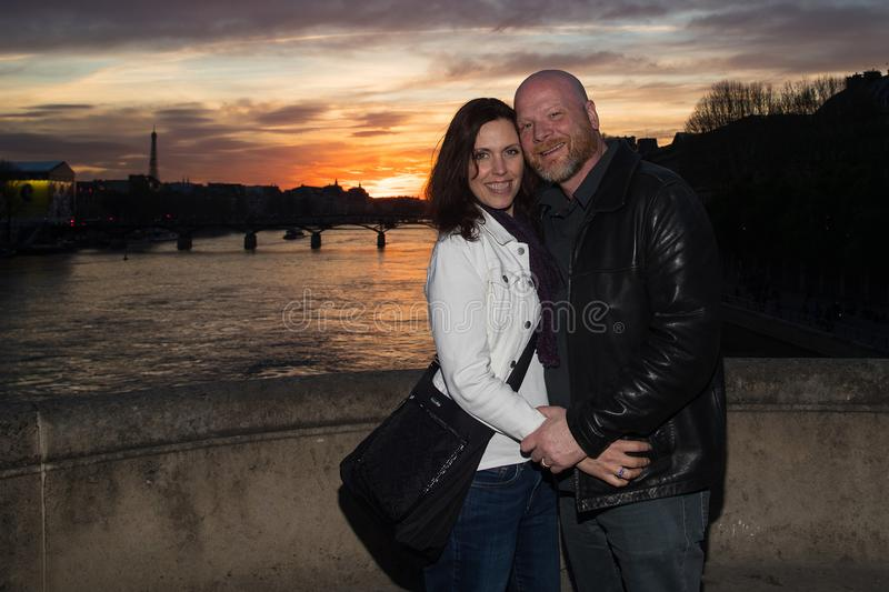 Romantic Couple in love on the Seine River in Paris, France. Man and women pose for a photo under French sunset stock photography
