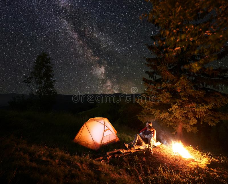 Romantic couple in love sits on log at the camping, hugging and admire the scenery mighty mountains. Romantic couple hikers sitting on log beside illuminated royalty free stock images