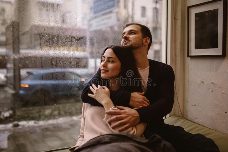 Romantic couple. Loving guy hugs his beautiful girlfriend sitting on the windowsill in a cozy cafe. stock image