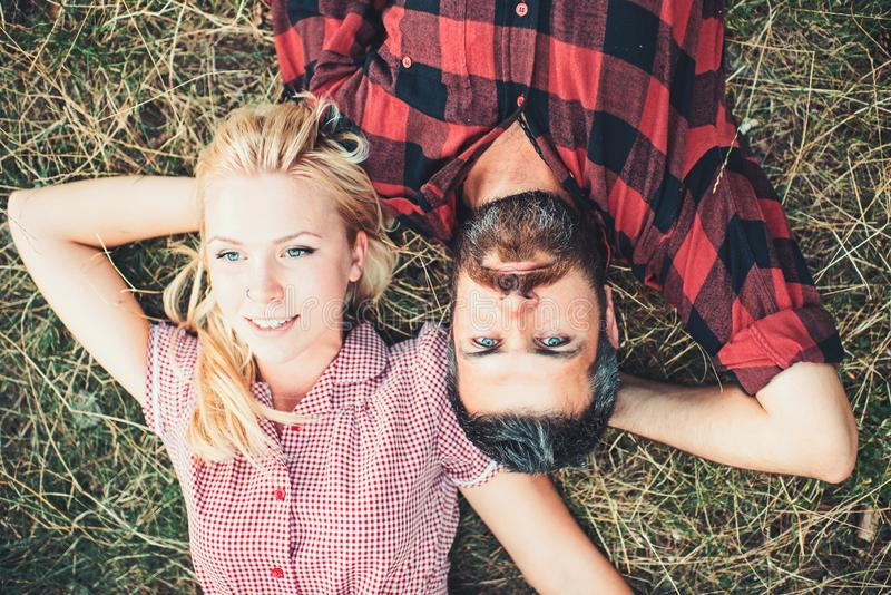 Romantic couple lying on grass in park. Young people relaxing with arms bent and hands beneath their heads view from royalty free stock image