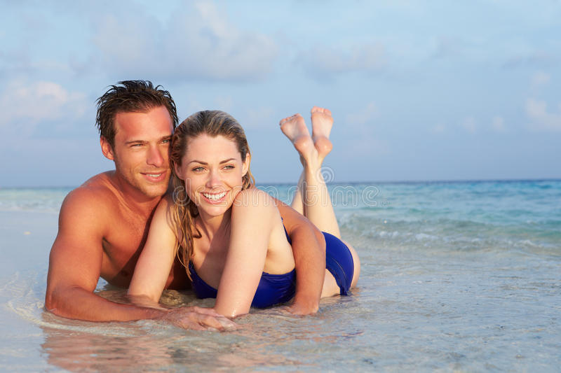 Romantic Couple Lying In Sea On Tropical Beach Holiday Stock Image