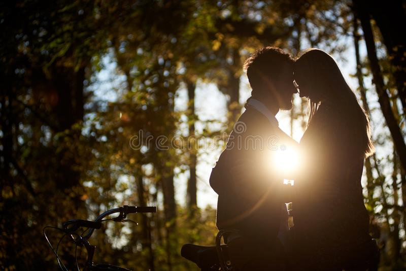 Romantic couple, man and attractive girl close together at tandem bicycle in dark autumn park. royalty free stock photo