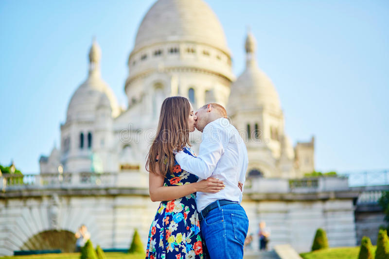 Romantic couple near Sacre-Coeur cathedral on Montmartre, Paris. Romantic couple kissing near Sacre-Coeur cathedral on Montmartre, Paris royalty free stock photography