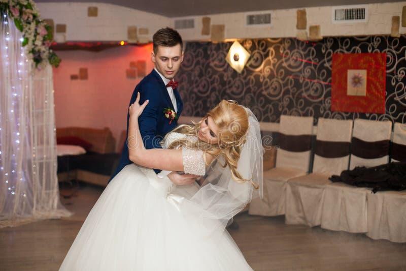 Romantic couple of newlyweds first elegant dance at wedding reception hall stock photo