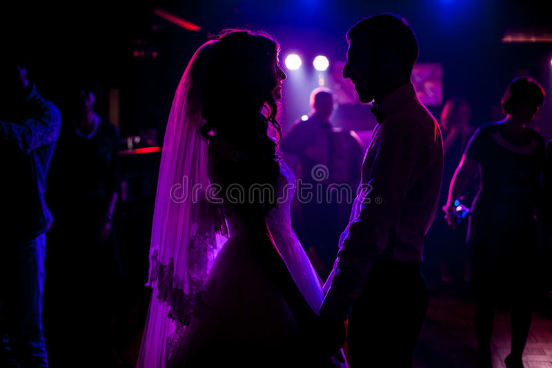 Romantic couple of newlyweds silhouettes posing at wedding stock images