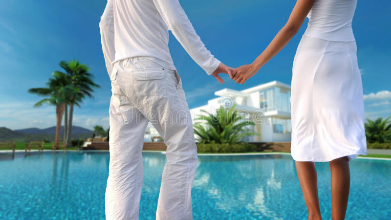 Romantic couple overlooking their dream villa. View from behind of a romantic couple standing holding hands overlooking their dream modern whitewashed tropical stock illustration