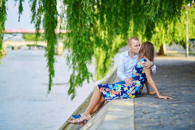 Romantic couple in Paris on a summer day. Romantic couple sitting on the Seine embankment on a hot summer day in Paris royalty free stock photos