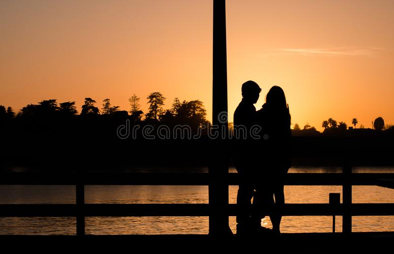 Romantic couple on a pier in Santa Cruz hugging during sunset royalty free stock image