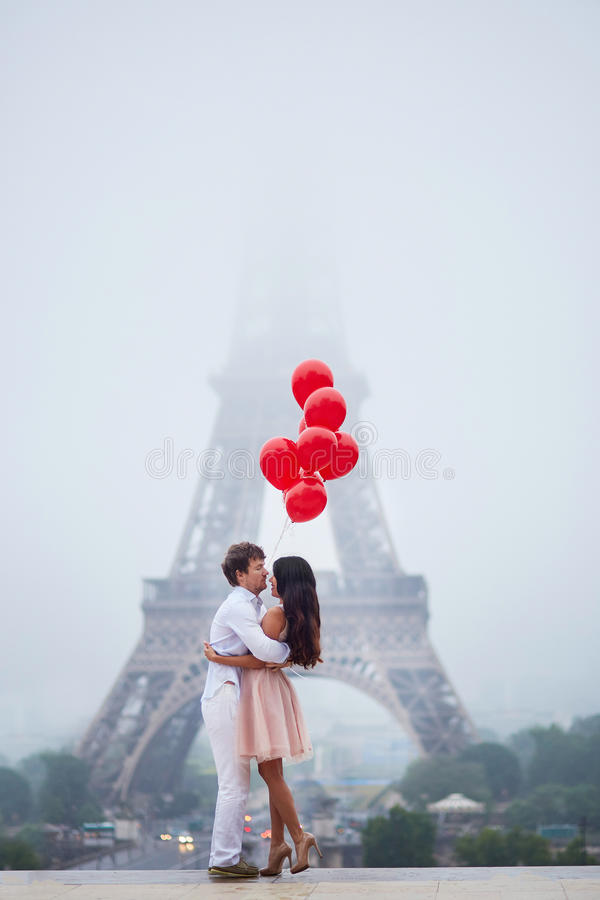 Romantic couple with red balloons together in Paris. Beautiful romantic couple in love with bunch of red balloons together near the Eiffel tower in Paris on a stock photo